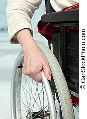 Close-up of a woman's hand on the wheel of her wheelchair