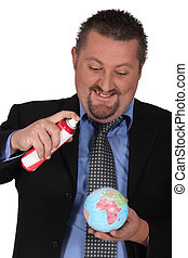 Businessman spraying a globe with an aerosol