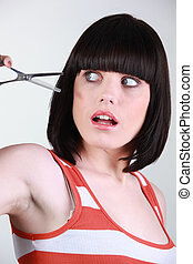 Woman scared of a pair of hairdressing scissors