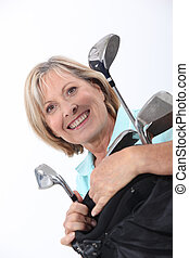 Smiling senior woman with golf equipment