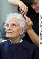 Combing Out the Curls - Attractive senior getting her hair...