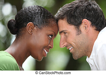 Close up of a mixed race couple touching foreheads