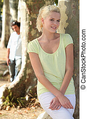Man watching woman leaning on tree trunk