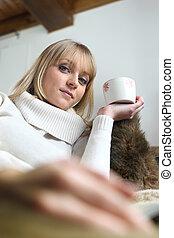 Woman sat on sofa with mug