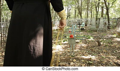The priest at the cemetery - August 6, 2012 Ufa, Russia The...