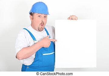 Surprised tradesman holding a blank sign