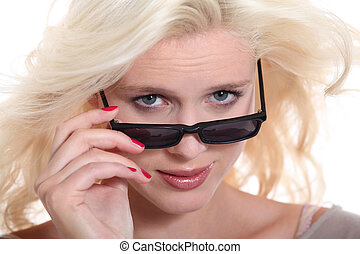 Blonde woman peering over her sunglasses