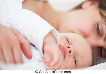 Woman and her baby lying side by side in a room