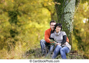 Couple sitting by a tree