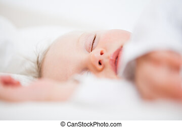 Baby falling asleep while extending her arms in a bedroom