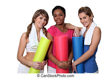 Young women going to yoga class together