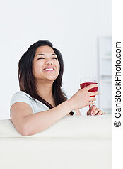 Woman smiles as she holds a glass of red wine