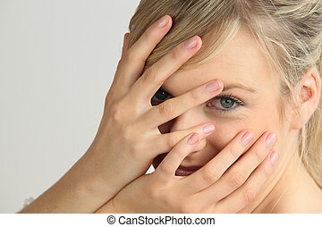 Blond woman with hands on face