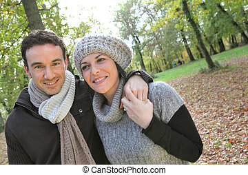 Couple walking through brown leaves