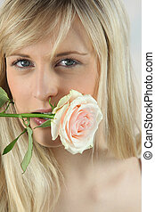 Blonde woman with rose in mouth