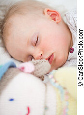 Cute baby sleeping next to her stuffed teddy bear in a...