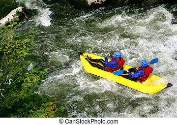 Two people kayaking down river rapids