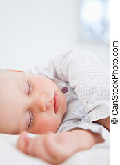 Baby sleeping while extending her arm in a bedroom