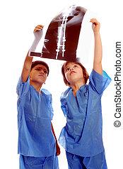 Studying the X-ray - Two children in scrubs studying an...