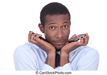 Man looking confused holding two mobile telephones