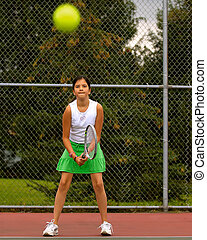 Playing Tennis - Middle school tennis player standing in...