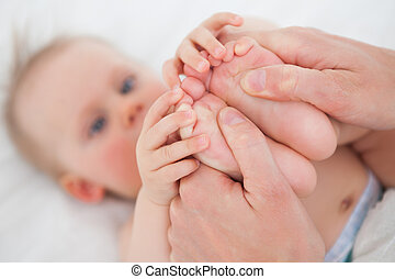 Feet of a cute little girl being held indoors