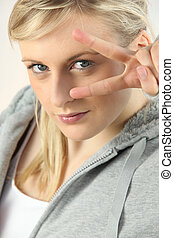 Blonde woman with fingers in V shape