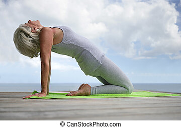 Senior woman doing yoga on a jetty
