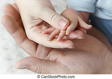 Hands of mother, father and baby - Three hands of mother,...