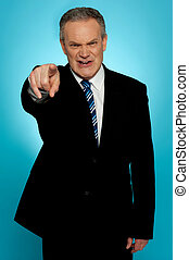 Angry senior businessman pointing finger at you isolated...