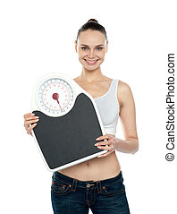 Healthy young woman with a weighing scale