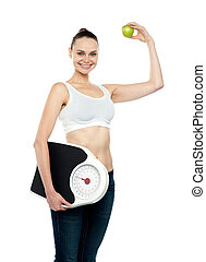 Fit woman holding weighing machine and green apple -...