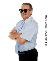 Confident male executive wearing sunglasses and posing with...