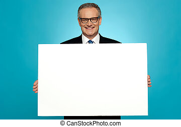 Business representative holding blank ad board and smiling...