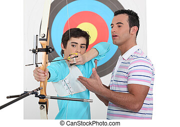A father teaching his son how to shoot a bow.