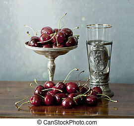 Cherries on a silver plate and an ancient glass