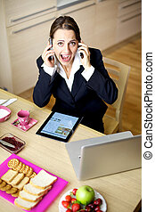 Businesswoman shouting talking with two phones at home -...