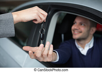 Man receiving car keys while sitting in his car in a garage