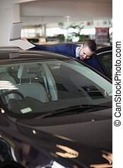 Dealer looking into a car in a dealership