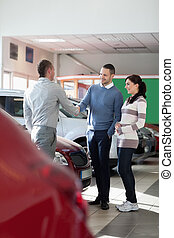 Car dealer shaking hand with a man in a car shop