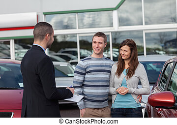 Salesman talking to a couple in a dealership