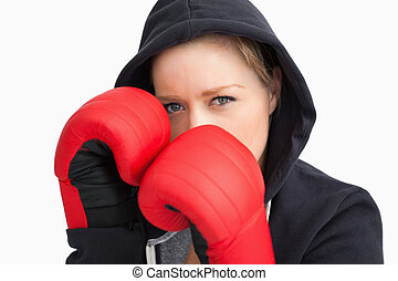 Woman with hoodie boxing against white background