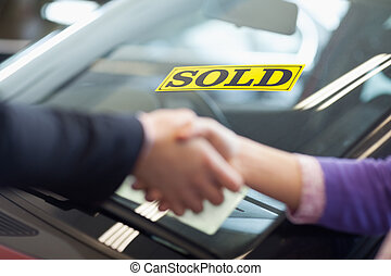 People shaking hands in front of a sold car