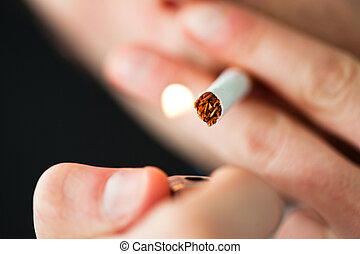 Close up of a man lighting a cigarette against a black...