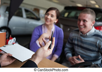 Couple listening to a car dealer in a car shop
