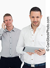 Two smiling men using phone and tablet computer against a...
