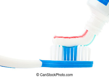 Close up of a tube of toothpaste with a toothbrush