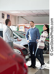 Smiling couple talking with a car dealer in a car shop