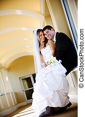 Newlywed couple in love - a bride and her groom, she is...