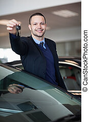 Dealer holding car keys in a dealership